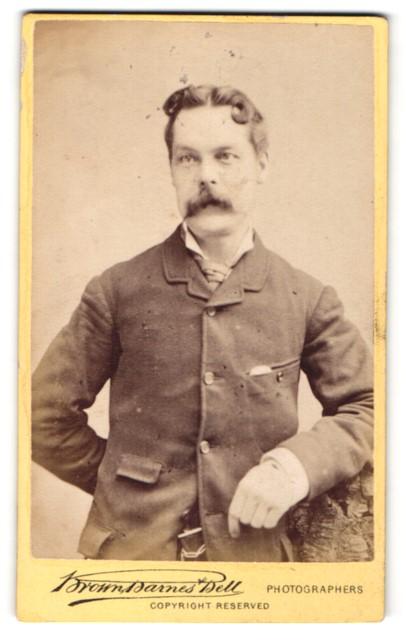 Fotografie Brown Darnes Bell, London, Liverpool, Portrait lächelnder Herr mit Schnauzbart in zeitgenössischer Kleidung