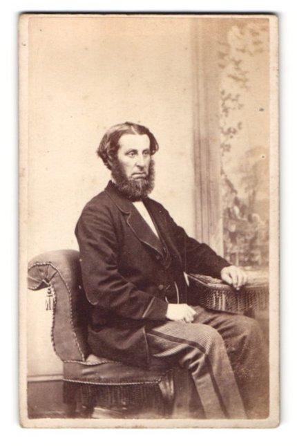Fotografie J. Evans, unbekannter Ort, Portrait älterer Herr mit Bart in zeitgenössischer Kleidung am Tisch sitzend