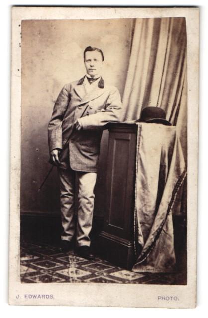 Fotografie J. Edwards, Scarboro, Portrait junger Herr in zeitgenössischer Kleidung mit Stock u. Hut an Sockel gelehnt