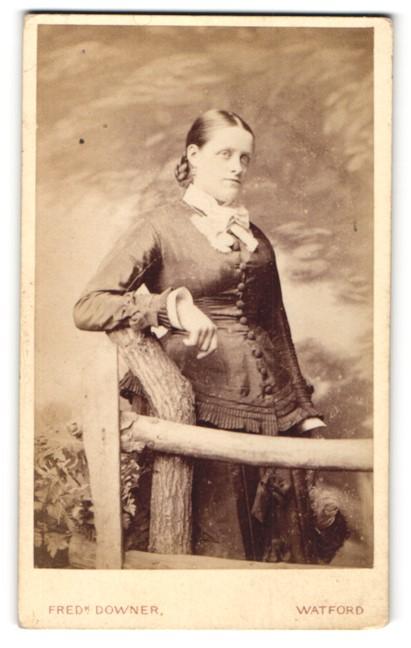 Fotografie Fred Downer, Watford, Portrait junge Dame in zeitgenössischer Kleidung an einem Zaun lehnend