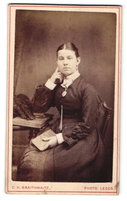 Fotografie C. H. Braithwaite, Leeds, Portrait, Portrait junge Dame mit Amulett u. Buch am Tisch sitzend