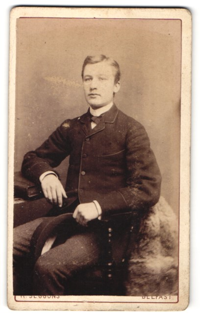 Fotografie Seggons, Belfast, Portrait junger charmanter Herr in zeigenössischer Kleidung mit Buch am Tisch sitzend