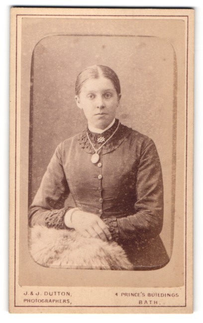 Fotografie J. & J. Dutton, Bath, Portrait junge Dame mit Amulett u. zurückgebundenem Haar an Fell gelehnt
