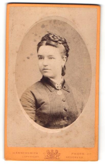 Fotografie Hammersmith, London, Portrait junge Dame mit Flechtfrisur und Amulett in zeitgenössischer Kleidung
