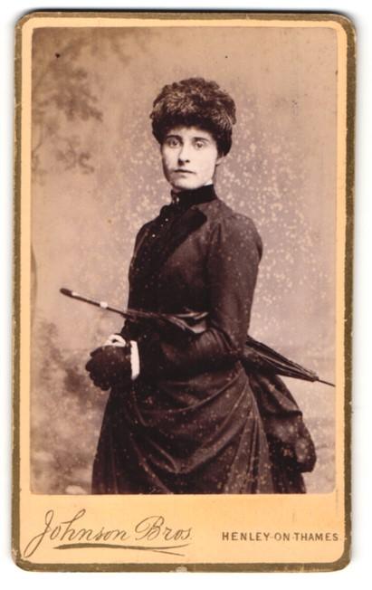 Fotografie Johnson Bros., Henley-on-Thames, Portrait junge Dame mit Schirm unter dem Arm und Handschuhen