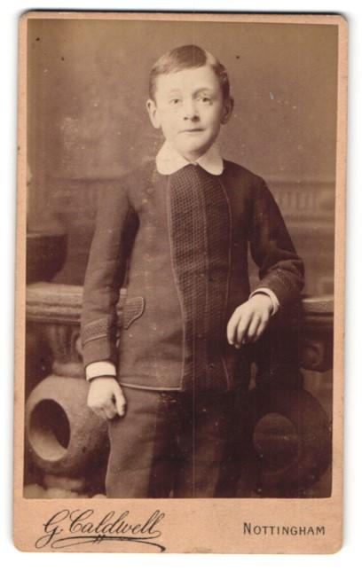 Fotografie G. Caldwell, Nottingham, Portrait kleiner Junge mit Seitenscheitel an Brüstung gelehnt