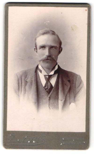 Fotografie Duysharte & Co., Chelmsford, Portrait bürgerlicher Herr mit Schnauzbart u. Krawatte im Anzug