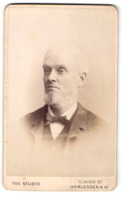 Fotografie The Studio, Harlesden N. W., Portrait älterer Herr mit Bart u. Fliege im Anzug