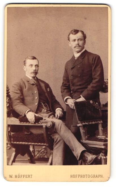 Fotografie W. Höffert, Berlin, Hamburg, Portrait zwei junge Herren in Anzügen auf Stuhl sitzend und an Tisch gelehnt