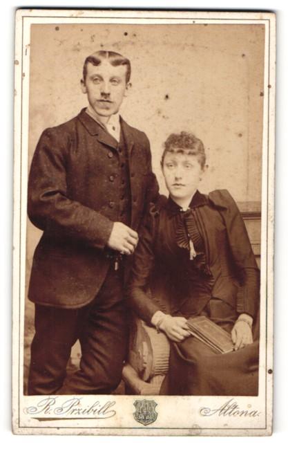 Fotografie R. Przibill, Altona, Portrait junge Dame mit zurückgeb. Haar u. Buch auf Stuhl sitzend und Herr im Anzug