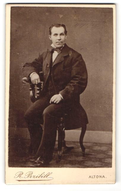 Fotografie R. Przibill, Altona, Portrait charmanter Herr mit Fliege im Anzug auf Stuhl sitzend
