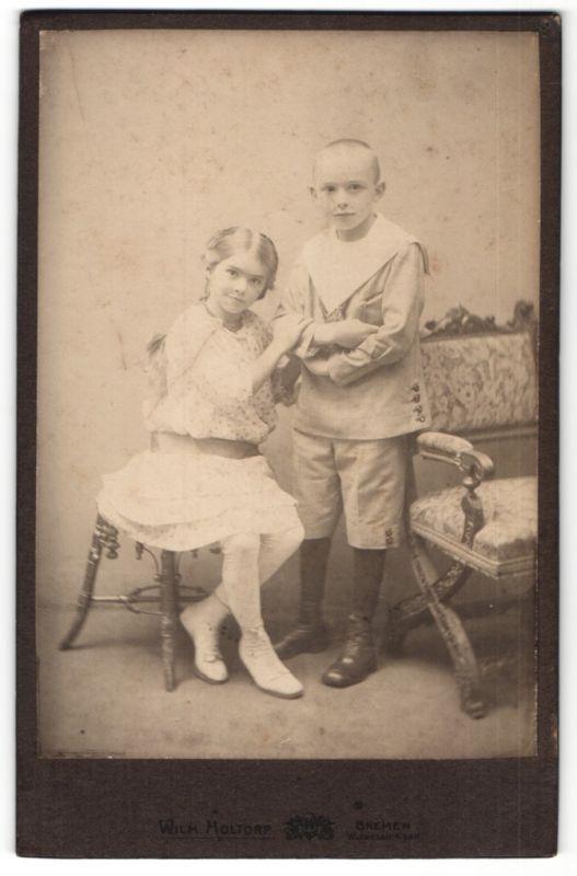 Fotografie Wilh. Holtorp, Bremen, Portrait Bub und Mädchen in zeitgenöss. Kleidung
