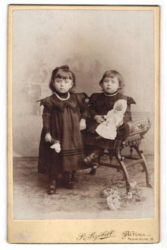 Fotografie R. Przibill, Hamburg-Altona, Portrait zwei Kleinkinder in identischer Kleidung mit Puppe