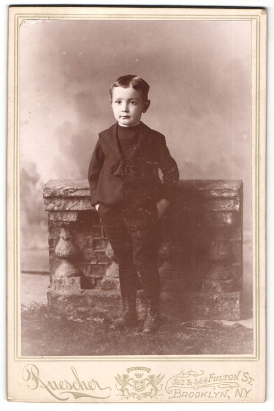 Fotografie Ruescher, Brooklyn, NY, Portrait kleiner Bub mit Händen in den Taschen