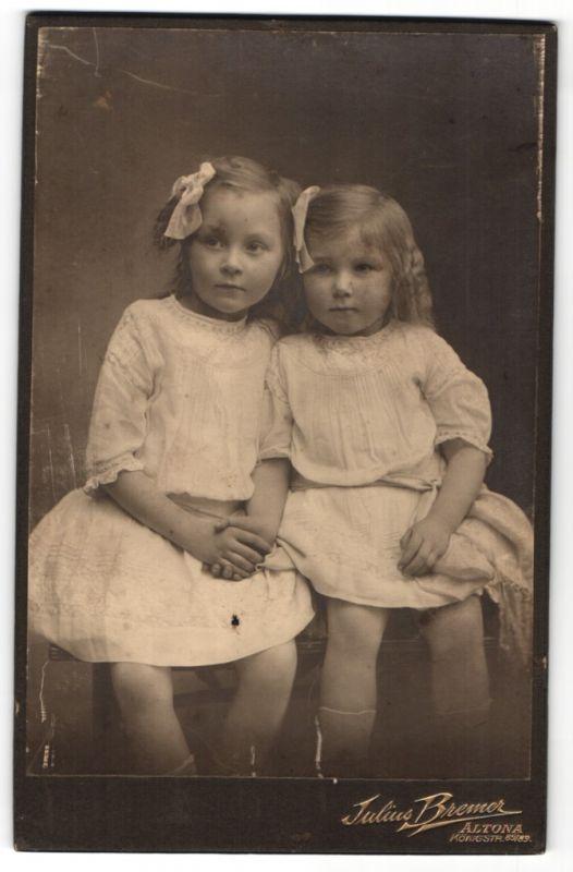 Fotografie Julius Bremer, Hamburg-Altona, Portrait zwei kleine Schwstern in identischen Kleidern