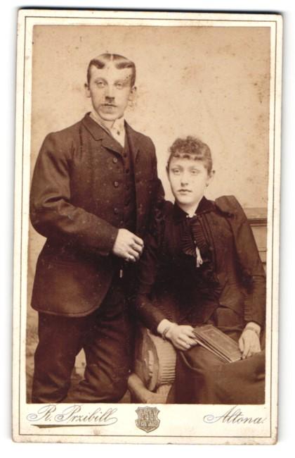 Fotografie Rudolf Przibill, Altona, Mann mit Mittelscheitel und Frau mit Buch im Schoss