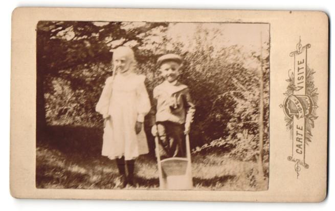 Fotografie Fotograf unbekannt, Ort unbekannt, Mädchen und Junge mit Schubkarre im Freien