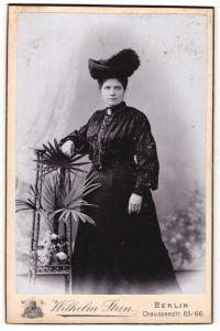 Fotografie Wilhelm Stein, Berlin, Portrait elegante junge Dame in schwarz mit Hut