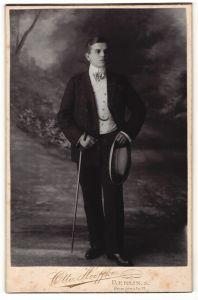 Fotografie Otto Hoeffke, Berlin-S, Portrait junger Herr in Abendgarderobe mit Spazierstock und Hut