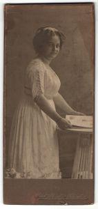 Fotografie Paul Schindler, Wittenberg, Bürgertochter in weissem Kleid blättert in einer Zeitschrift