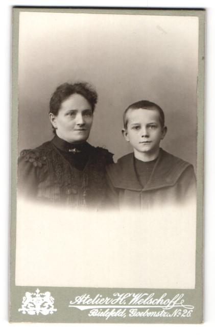 Fotografie Atelier H. Welschoff, Bielefeld, Portrait Mutter mit Kragenbrosche im eleganten Kleid u. Sohn