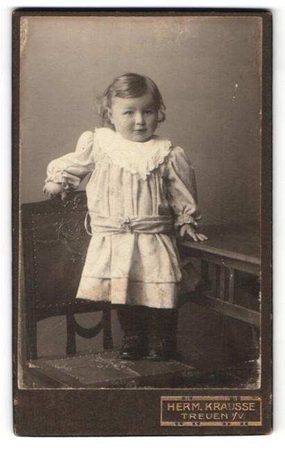 Fotografie Herm. Krausse, Treuen i / V., Portrait niedliches kleines Mädchen im hübschen Kleid auf Stuhl stehend