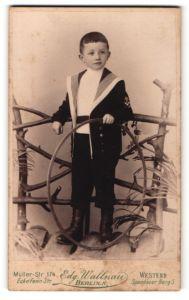 Fotografie Edg. Wallnau, Berlin N., Portrait kleiner Junge im Matrosenanzug mit Reifen an Geländer gelehnt