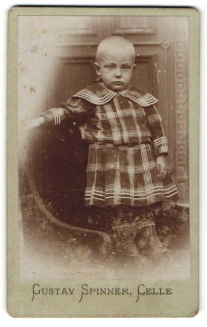 Fotografie Gustav Spinner, Celle, Portrait Kind mit geschorenem Kopf in kariertem Kleid