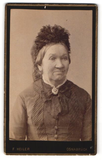 Fotografie F. Heiler, Osnabrück, Portrait ältere lächelnde Dame mit Haube u. Kragenbrosche in zeitgenöss. Kleidung