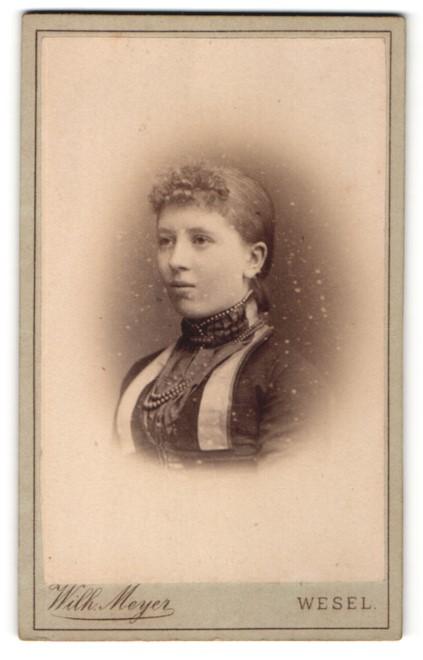 Fotografie Wilh. Meyer, Wesel, Portrait junge hübsche Dame mit zurückgebundenem Haar in festlicher Kleidung