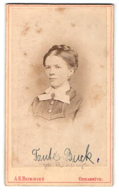 Fotografie A. H. Heckmann, Osnabrück, Portrait junge lächelnde Dame mit Flechtfrisur und Ohrringen