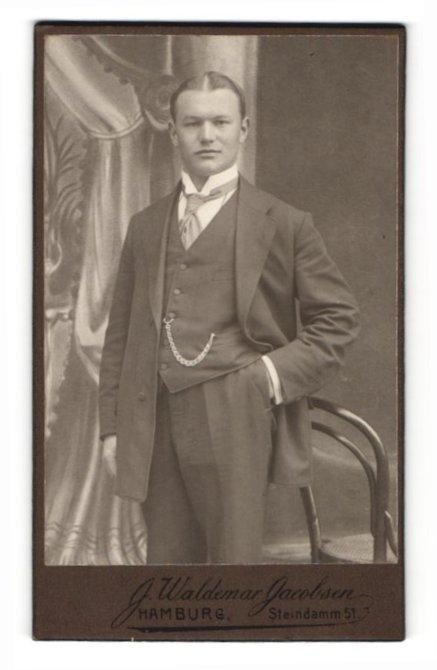 Fotografie J. Waldemar Jacobsen, Hamburg, Portrait charmanter Herr mit Mittelscheitel und Krawatte im Anzug