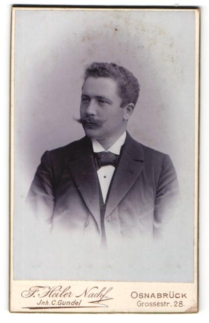 Fotografie F. Heiler Nachf., Osnabrück, Portrait charmanter Herr mit Zwirbelbart u. Fliege im Anzug