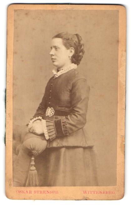 Fotografie Oskar Strensch, Wittenberg, Portrait lächelnde Dame mit Flechtfrisur in eleganter Kleidung an Sessel gelehnt