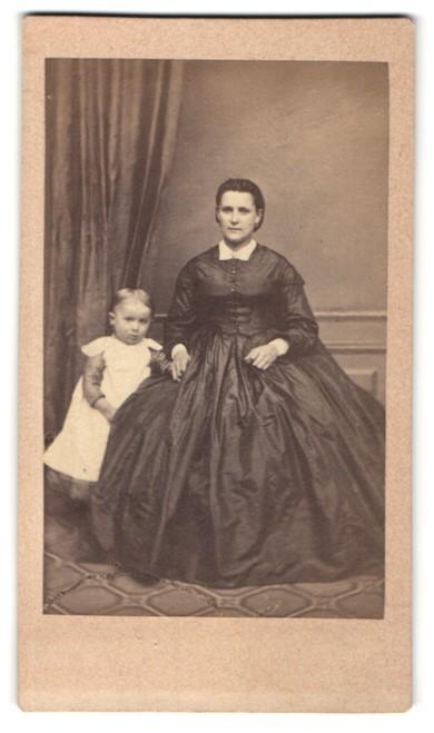 Fotografie unbekannter Fotograf und Ort, Portrait lächelnde Mutter im Festkleid auf Stuhl sitzend mit Kind