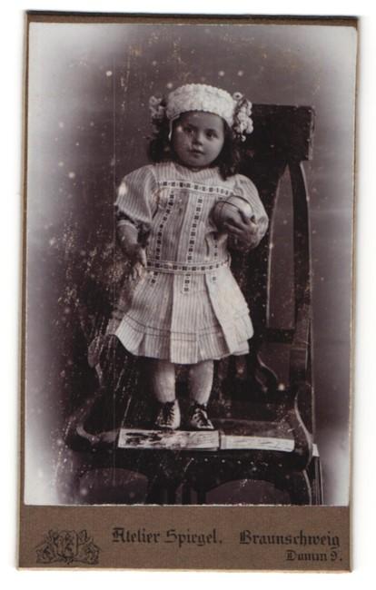 Fotografie Atelier Spiegel, Braunschweig, Portrait kleines Mädchen mit Ball in hübschem Kleid auf Stuhl stehend