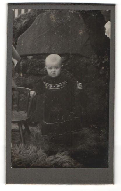 Fotografie W. Lüdecke, Hannover, Portrait niedliches Kleinkind im hübschen Kleid an Stuhl gelehnt