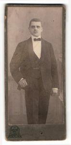 Fotografie Tietz, Berlin, Portrait eleganter junger Herr im Anzug mit Fliege