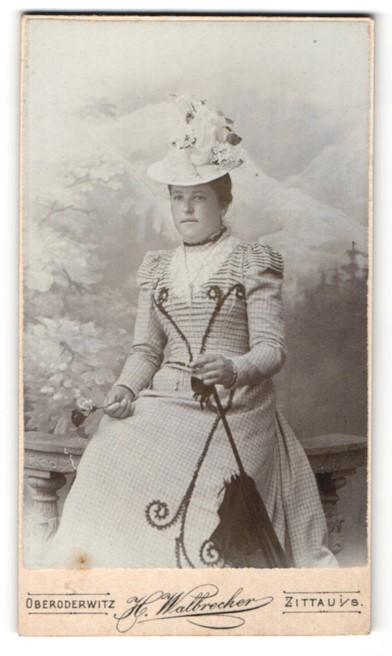 Fotografie H. Walbrecker, Zittau i. S., Dame mit aufwendig besticktem Kleid, Hut und Schirm
