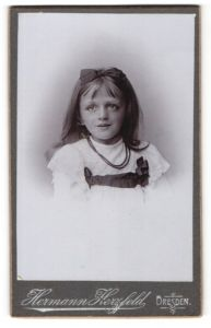 Fotografie Hermann Herzfeld, Dresden, Portrait kleines Mädchen mit Schleif und Perlenkette im hübschen Kleid