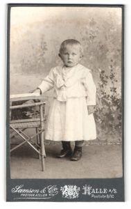 Fotografie Samson & Co., Halle a / S., Portrait niedliches Kleinkind im weissen Kleid an Stuhl gelehnt