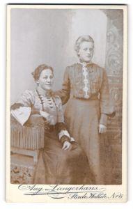 Fotografie Aug. Langerhans, Stade, Portrait lächelnde Dame mit zurückgebundenem Haar auf Hocker sitzend mit junger Dame