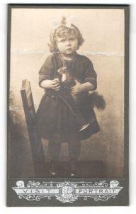 Fotografie Atelier Visit Portrait, Ort unbekannt, kleines Mädchen mit Schleife in Haar und Stofftier