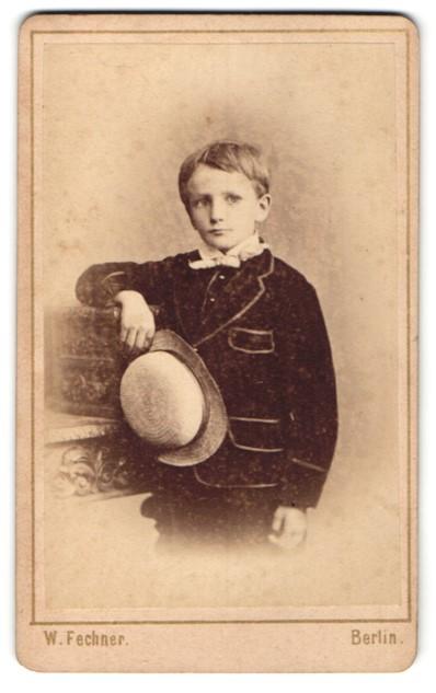Fotografie W. Fechner, Berlin, Portrait kleiner Junge mit Hut im Anzug an Tisch gelehnt