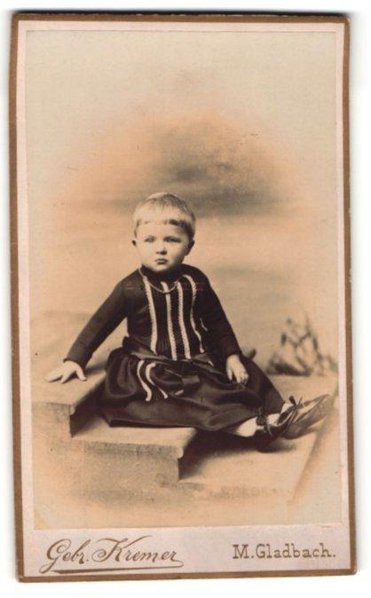 Fotografie Gebr. Kremer, M. Gladbach, kleines Mädchen in gestreiftem Kleid mit Kette und Lackschuhen