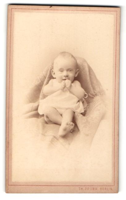 Fotografie Th. Prümm, Berlin, lachendes Baby in Hemdchen mit nackten Beinen