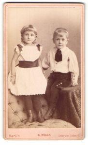 Fotografie H. Noack, Berlin, Portrait kleines Mädchen im hübschen Kleid auf Sessel stehend u. Junge auf Tisch sitzend