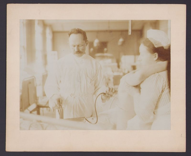 Fotografie S.F. Meissl, Berlin, Arzt entnimmt Flüssigkeit, Krankenschwester fixiert den Patient