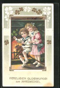 Präge-AK Junge im Matrosenanzug auf einem Steckenpferd u. Mädchen, Neujahrsgruss