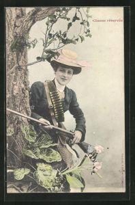 AK Chasse reservee, Jägerin mit Hut und Gewehr an Baum gelehnt